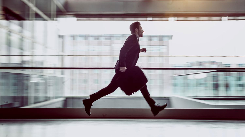 Ein Mann mit Aktentasche rennt über die Galerie in einem Bürohaus