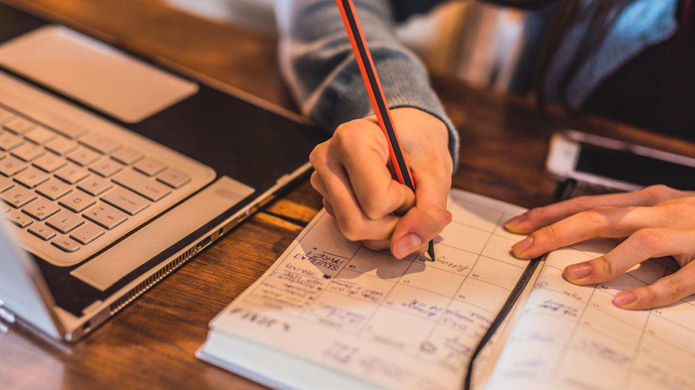 Eine Frau schreibt einen Termin in einen Kalender, der neben ihrem Laptop auf einem Schreibtisch liegt