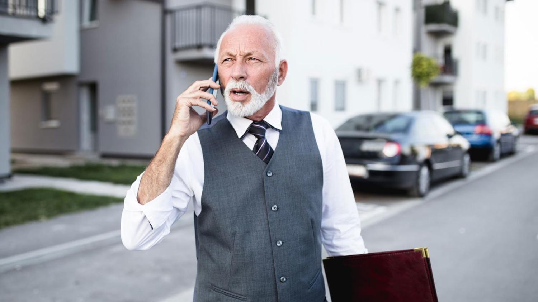 Senior telefoniert im Anzug, um eine Wohnung zu vermieten