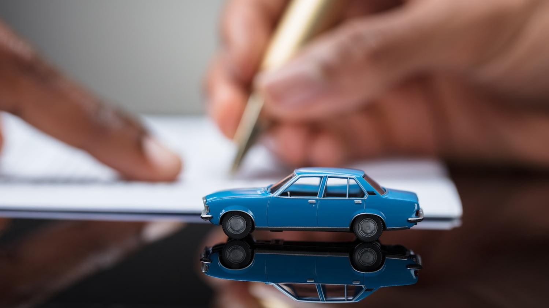 Im Vordergrund steht ein Spielzeugauto, im Hintergrund unterschreibt jemand einen Vertrag