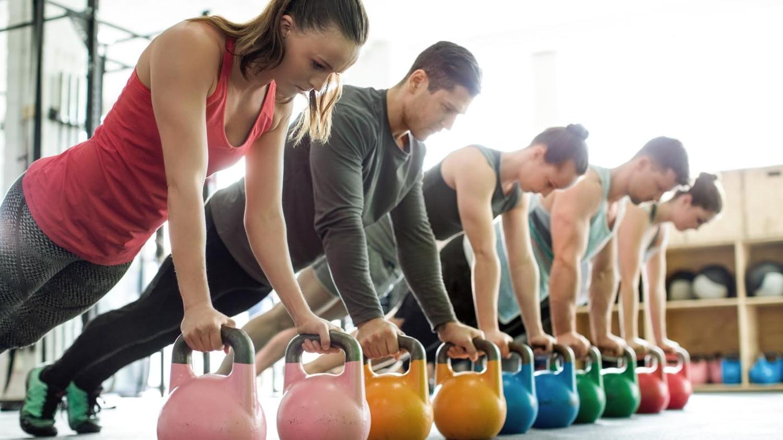 Sportliche junge Leute beim Training mit Kettlebells