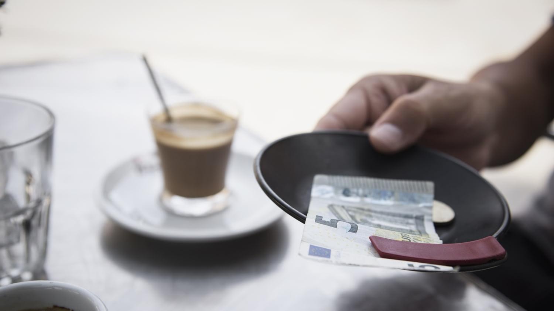 Ein Kunde hinterlässt 5 Euro als Trinkgeld auf einem Teller im Restaurant
