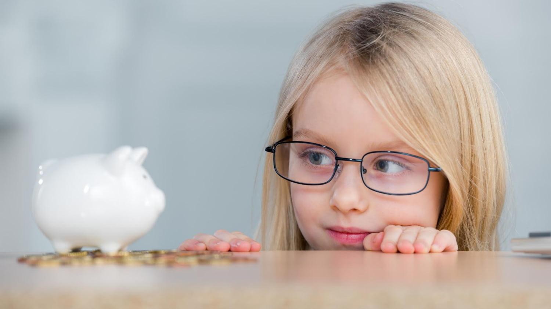 Mädchen blickt auf sein Sparschwein und einzelne Münzen