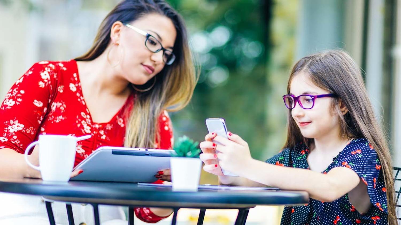 Tochter spielt mit dem Smartphone, während die Mutter ihr über die Schulter blickt