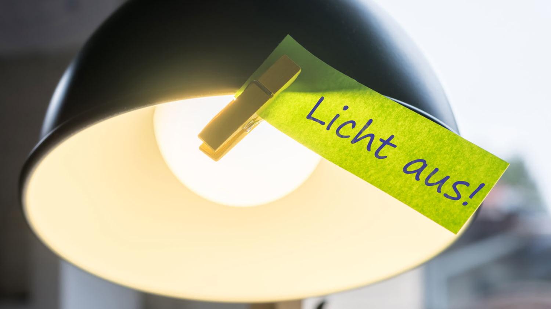 An einer Lampe hängt ein Zettel mit der Aufschrift Licht aus