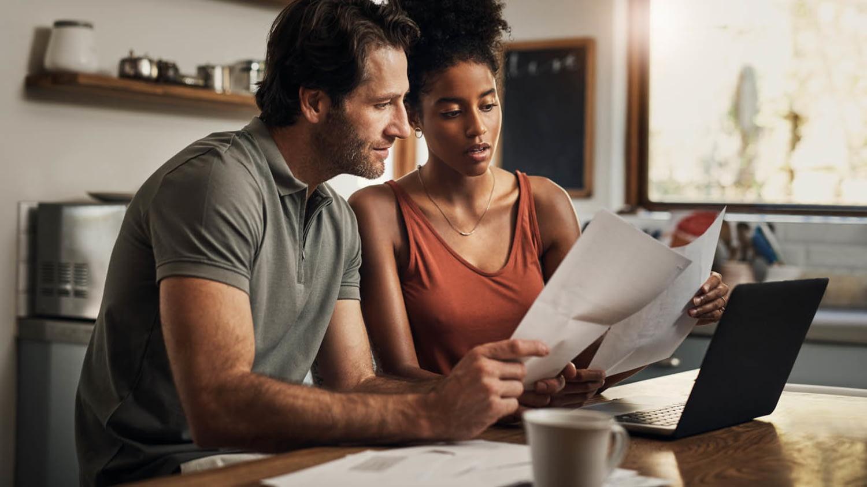 Paar sitzt mit einem Laptop vor sich am Küchentisch und geht Dokumente durch