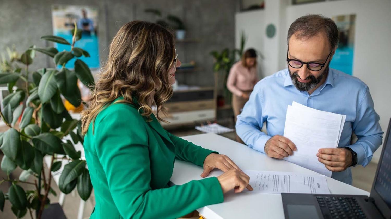 Ein Mann lässt sich von einer Bankmitarbeiterin ein Formular erklären