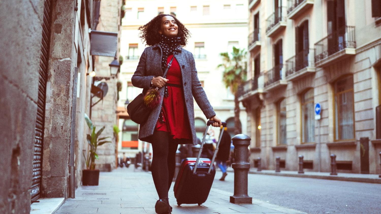 Eine junge Frau zieht ihren Koffer durch eine Straße in Barcelona und betrachtet lächelnd die Häuser