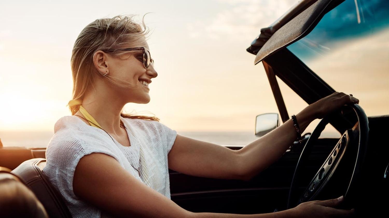 Eine Frau fährt im offenen Cabrio