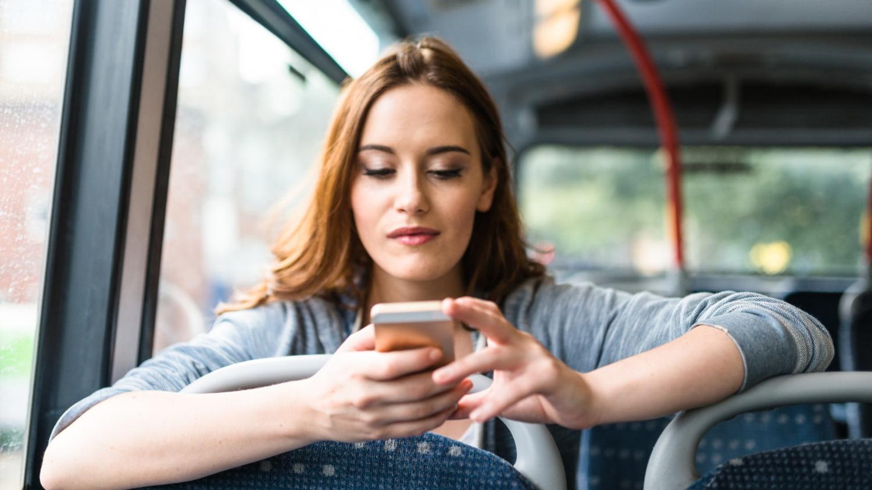 Eine junge Frau sitzt im Bus und sieht nachdenklich auf ihr Handy.