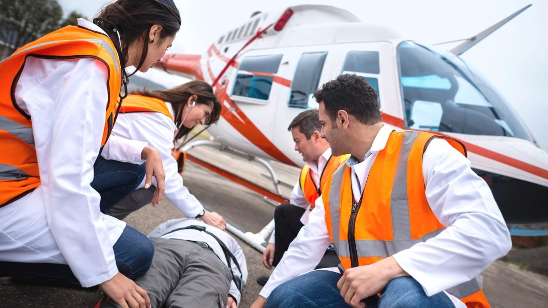 Rettungskräfte bereiten einen Mann auf einer Trage für den Krankentransport in einem Hubschrauber vor