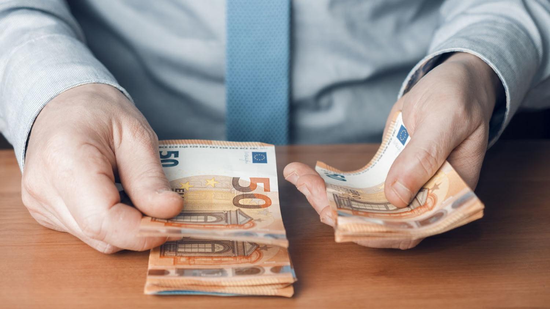 Bankangestellter zählt Bargeld in 50-Euro-Scheinen auf einem Holztisch
