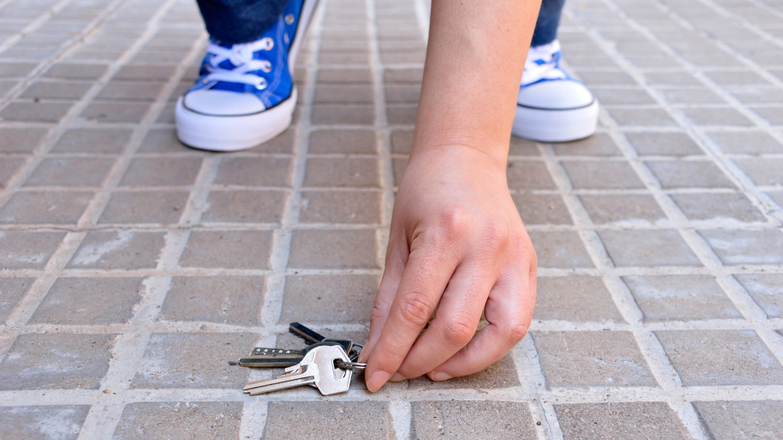 Ein Mann geht in die Knie und hebt einen Schlüssel vom Straßenpflaster auf