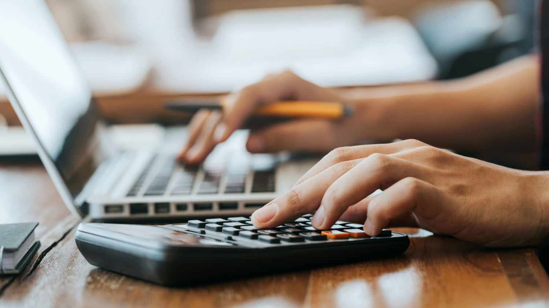 Ein Mann sitzt an einem Tisch mit der rechten Hand tippt er am Laptop mit der linken auf einen Taschenrechner