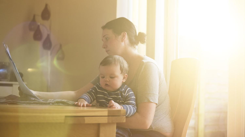Eine Mutter mit Kind blickt besorgt auf ein paar Unterlagen