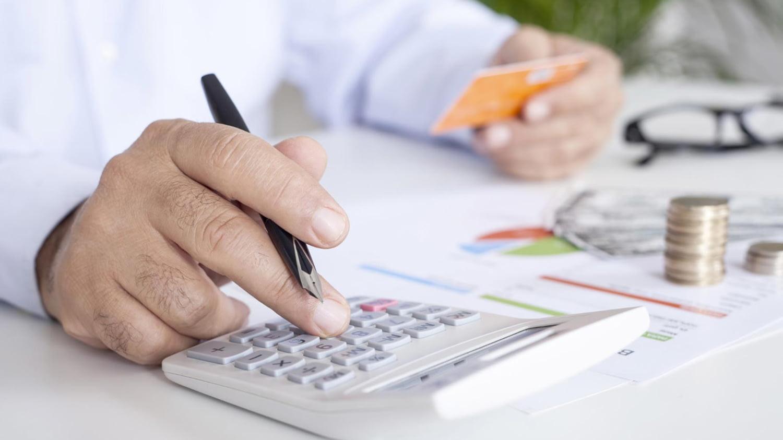 Mann am Schreibtisch hält in einer Hand eine Kreditkarte und tippt mit der anderen auf einem Taschenrechner