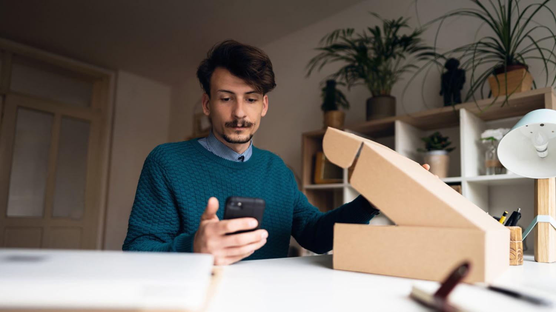 Junger Mann mit geöffnetem Paket vor sich und Smartphone in der Hand