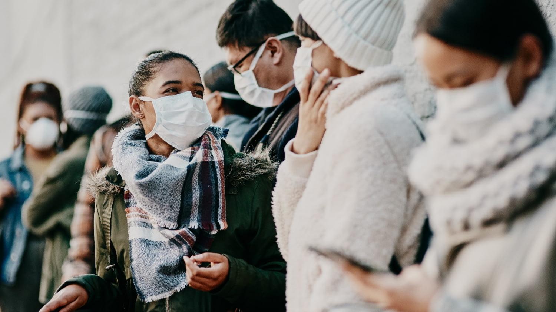 Menschen mit Mund-Nasen-Masken stehen zusammen in einer Gruppe