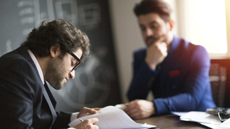 In Gegenwart eines Notars unterschreibt ein Mann im schwarzen Anzug ein Dokument