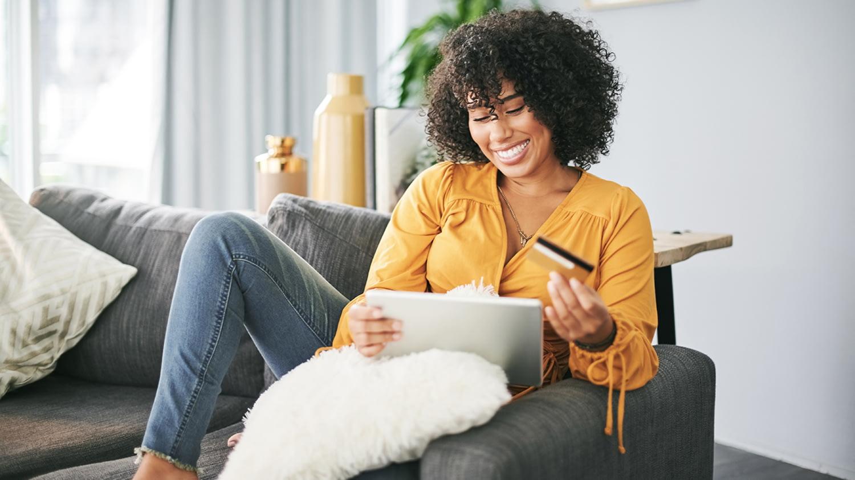 Junge Frau sitzt mit Tablet auf dem Sofa und bestellt etwas mit ihrer Kreditkarte