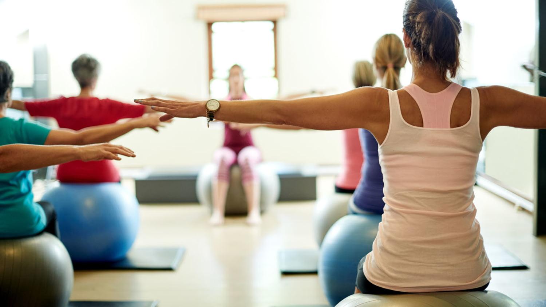 Gruppe von Frau trainiert auf einem Gymnastikball den Rücken