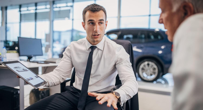 Engagierter junger Autoverkäufer macht einem Kunden ein attraktives Angebot