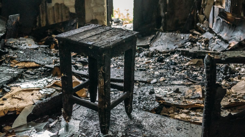 Hausratversicherung: Ein ausgebranntes Zimmer mit einem verkohlten Holzschemel im Mittelpunkt