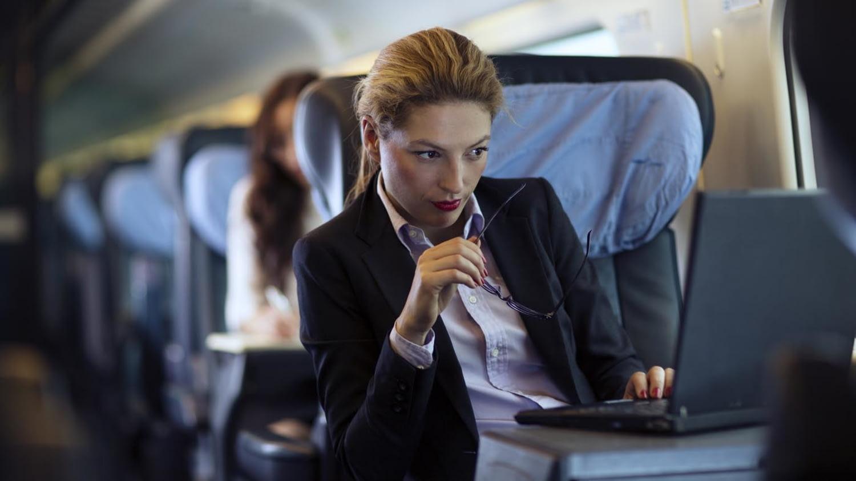 Dame im Businessanzug sitzt im Zug