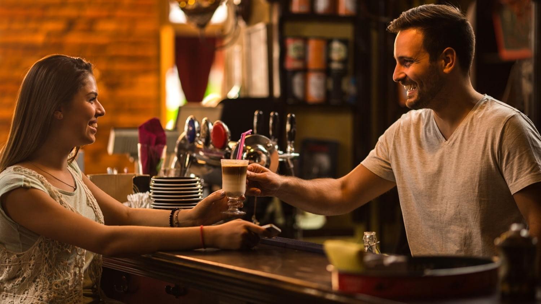 Junge Frau bekommt ihren Kaffee über den Tresen vom Barmann