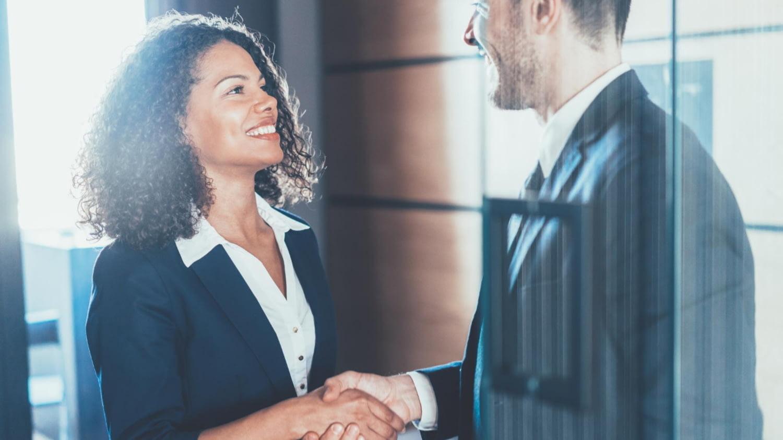 Frau und Mann im Business-Anzug reichen sich die Hände
