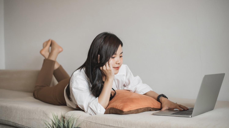 Eine junge Frau liegt entspannt auf dem Bauch auf dem Sofa und schaut auf ihren Laptop