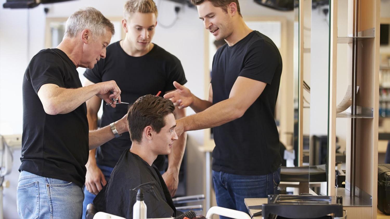 Drei Friseure stehen um einen Mann herum und schneiden an seinen Haaren