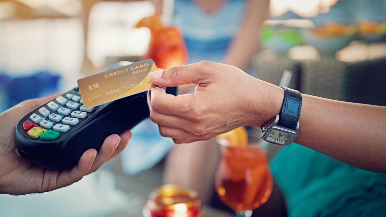 Eine Hand hält eine Kreditkarte über ein Kartenlesegerät. Im Hintergrund stehen Drinks auf einem Tisch