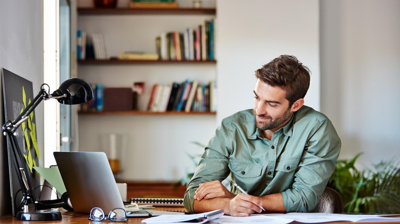 Mann sitzt am Schreibtisch, blickt auf einen Laptop und macht sich Notizen zu einzelnen Kreditangeboten
