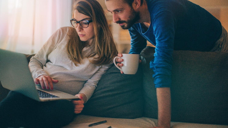 Junges Paar ausgestattet mit Notebook, Taschenrechner und Vertragsunterlagen beim Prüfen ihrer Finanzen