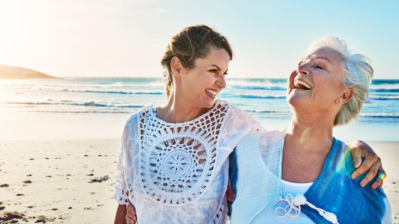 Seniorin und ihre Tochter spazieren Arm in Arm am Strand entlang